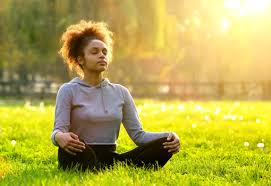 woman meditating in field during sunset